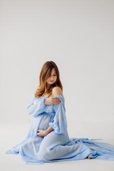 Mãe grávida elegante em vestido posando de orgulho de sua gravidez