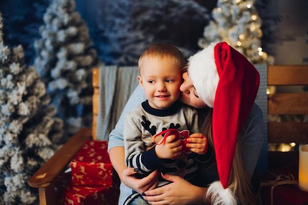 Mãe grávida, mantendo a criança pequena e sorrindo