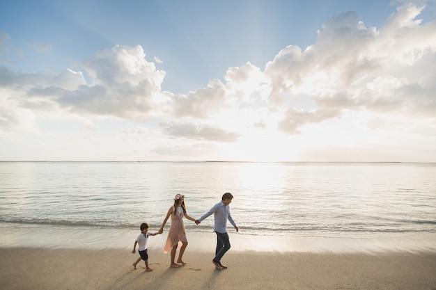 Mãe grávida, pai e filho caminhando na praia