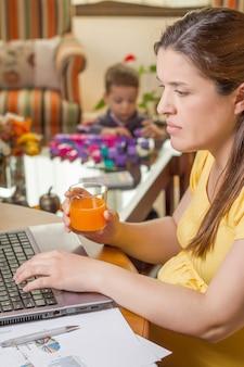 Mãe grávida trabalhando em casa com o filho