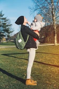 Mãe hippie com seu bebê vestido com roupas quentes caminhando em um dia ensolarado ao ar livre