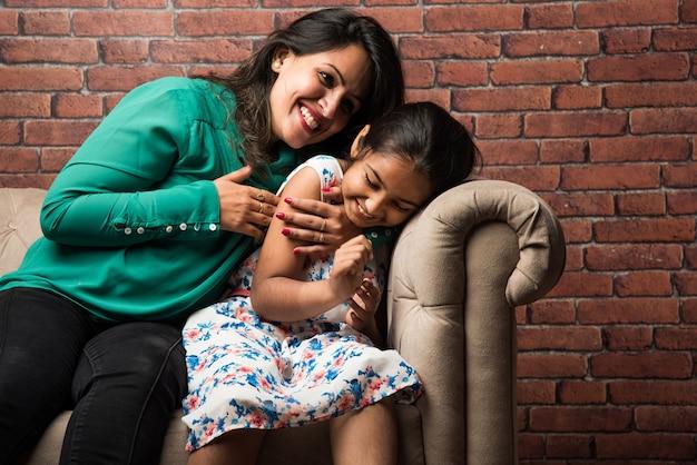 Mãe indiana e filha no sofá, acariciando, fazendo cócegas, foco seletivo