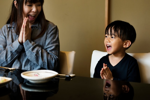 Mãe japonesa e filho rezando