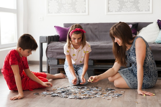 Mãe jogando quebra-cabeça com seus filhos em casa