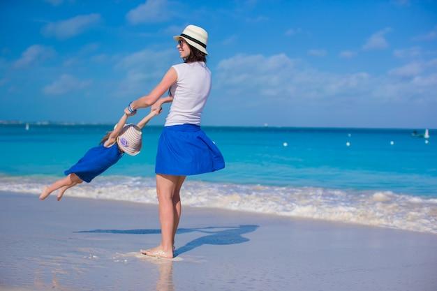 Mãe jovem e adorável filha se divertir na praia tropical
