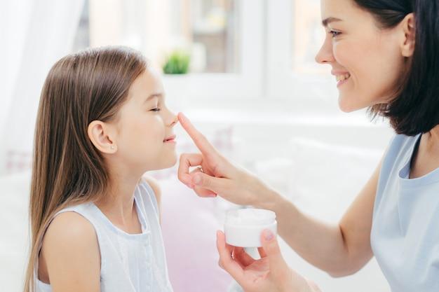 Mãe jovem e afetuosa toca o nariz da filha, segura o frasco de creme, desfruta a união, cuida da pele