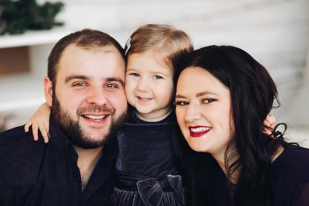 Mãe jovem e bonita com cabelo preto comprido e ondulado, pai forte e atraente com cabelo escuro curto passa o natal junto com sua filha pequena