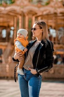Mãe jovem elegante caminha com o bebê no parque. mãe feliz