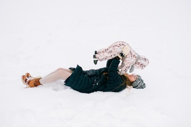 Mãe jovem feliz, brincando com seu bebê adorável no campo de inverno nevado.