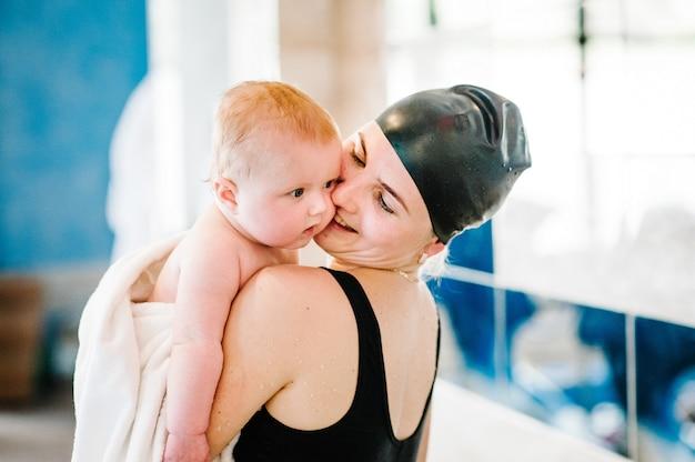 Mãe jovem feliz natação instrutor segurando um bebê nos braços a toalha.