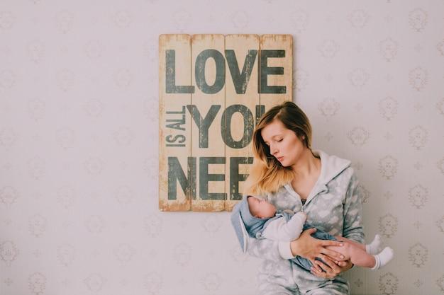 Mãe jovem feliz, segurando seu bebê infantil nas mãos no quarto