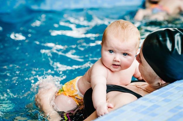 Mãe jovem, instrutor de natação e menina feliz na piscina para crianças. ensina criança infantil a nadar. aproveitar. mãe mantém criança mão se preparando para mergulhar. fazendo exercicios. bebê deitado no corpo da mãe