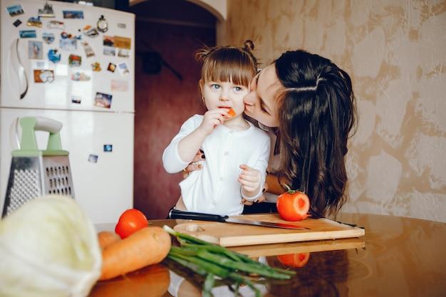 Mãe junto com sua filha cozinha legumes em casa na cozinha