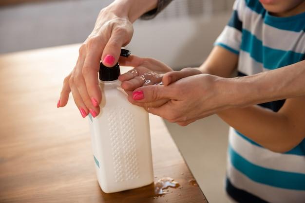 Mãe lavando as mãos do filho com cuidado no banheiro close-up. prevenção de infecção