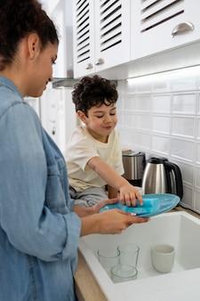 Mãe lavando pratos com o filho na cozinha