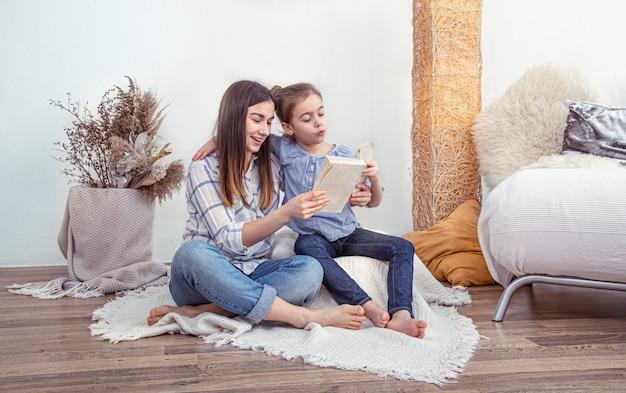 Mãe lê um livro com as filhas em casa.
