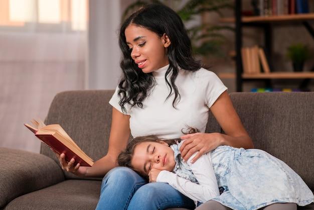 Mãe lendo a história da cama para a filha