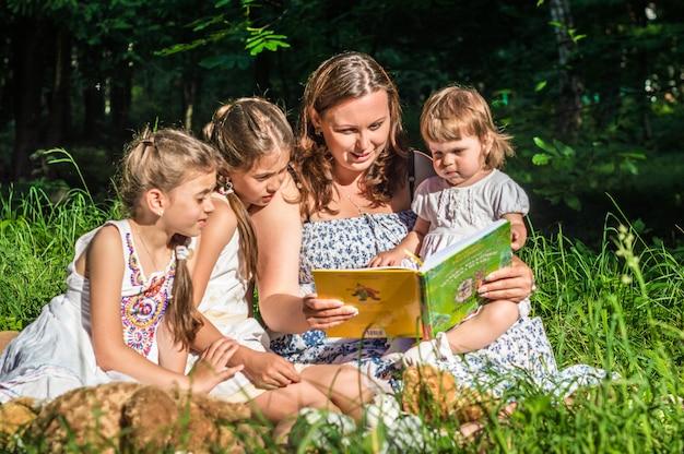 Mãe lendo livro com filhas