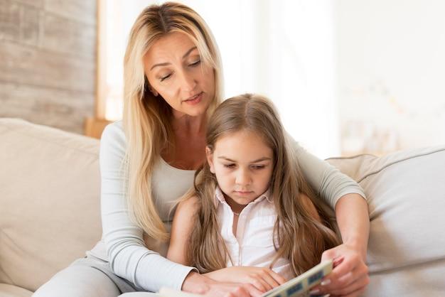 Mãe lendo livro para filha em casa