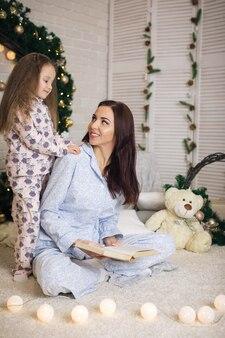 Mãe lendo livro para sua filhinha perto da árvore de natal em casa