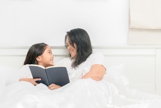 Mãe ler livro com filha juntos na cama