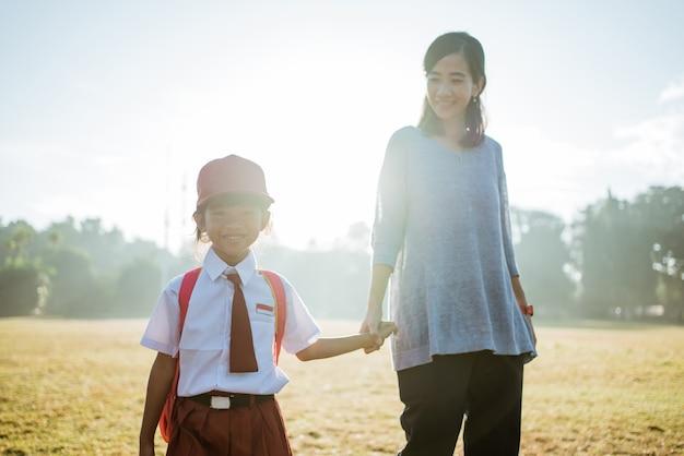 Mãe leva seu filho para a escola pela manhã