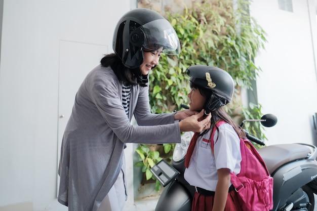 Mãe levando a filha para a escola de moto pela manhã. mãe aperta o capacete antes de ir de patinete para a escola