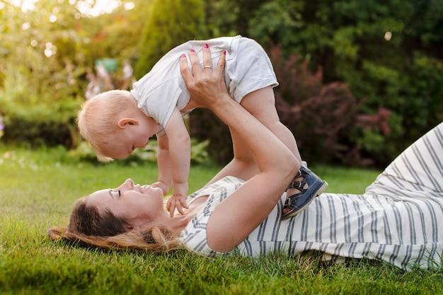 Mãe levanta seu bebê, ri e joga no verão na natureza maternidade