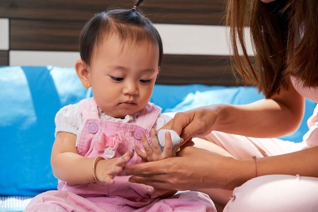 Mãe limpando as mãos da filha