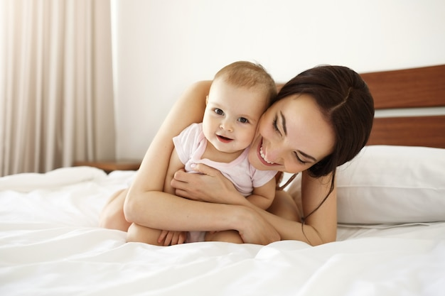 Mãe linda feliz em roupa de noite, deitada na cama com sua filha bebê abraçando sorrindo.