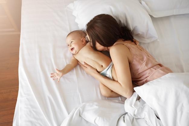 Mãe linda jovem e bebê recém-nascido, deitado na cama sorrindo enganando em casa. de cima.