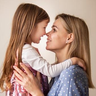 Mãe loira close-up, segurando a filha bonita