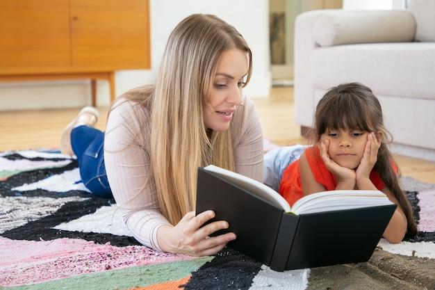 Mãe loira deitada no tapete com a filha e lendo o livro para ela.