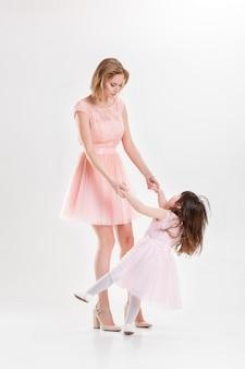 Mãe loira e doce filha em vestidos cor de rosa princesas abraçando e rindo em fundo cinza. família