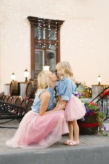 Mãe loira e filha em saias cor de rosa e camisas jeans se olham