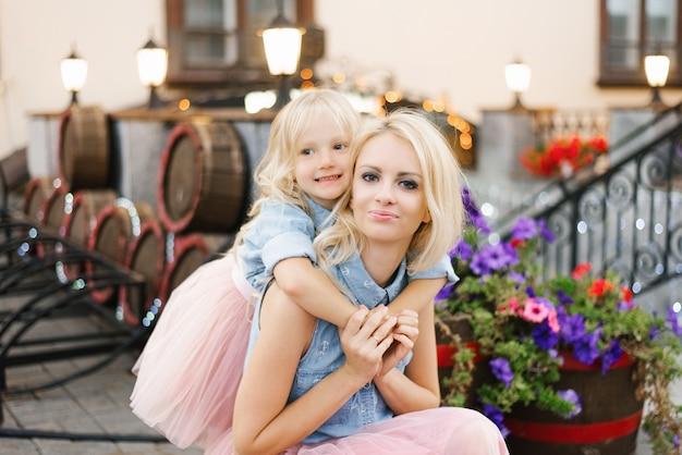Mãe loira e filha em saias rosa e camisas jeans.