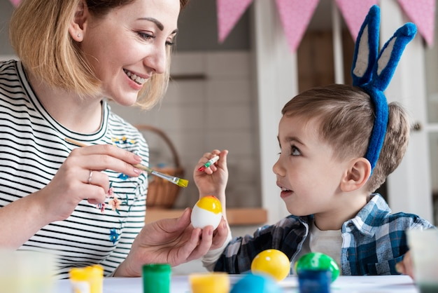 Mãe loira ensinando seu filho a pintar ovos para a páscoa