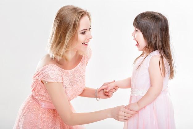 Mãe loira filha reconfortante em vestidos cor de rosa princesas em fundo cinza. bebê está chorando