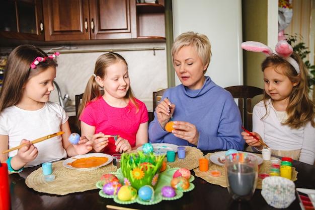 Mãe loira mostra às filhas como decorar ovos de páscoa em casa na cozinha.