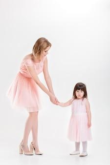 Mãe loira segurando a mão da doce filhinha em princesas de vestidos cor de rosa em fundo cinza. família