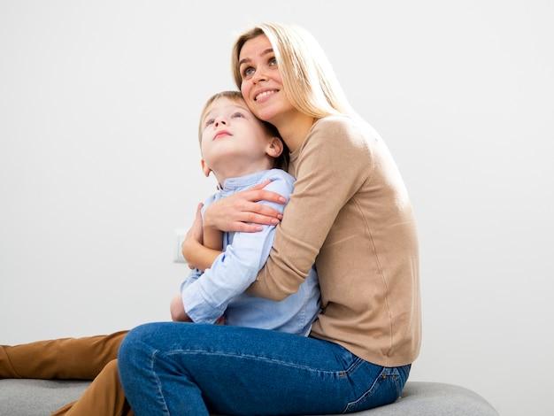 Mãe loira vista frontal, abraçando seu filho