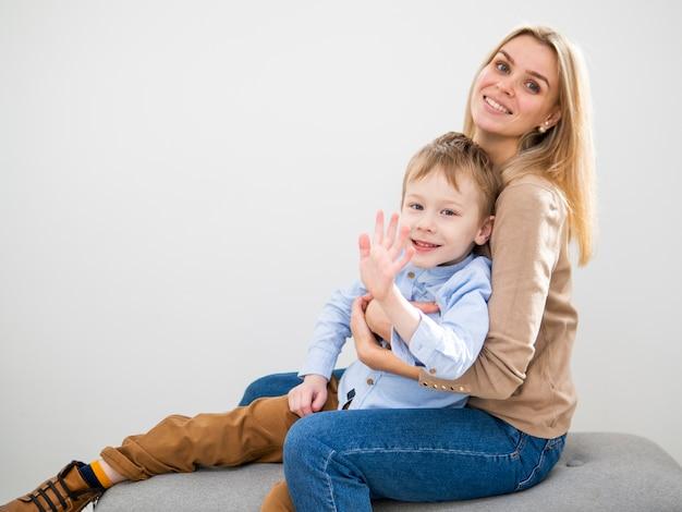 Mãe loira vista frontal, segurando o jovem rapaz
