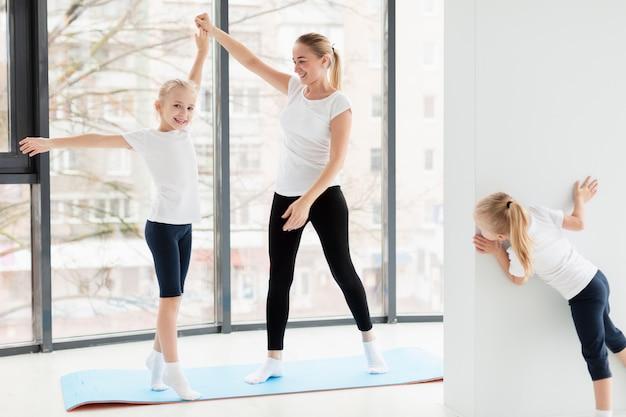 Mãe malhando com as filhas em casa no tapete de ioga