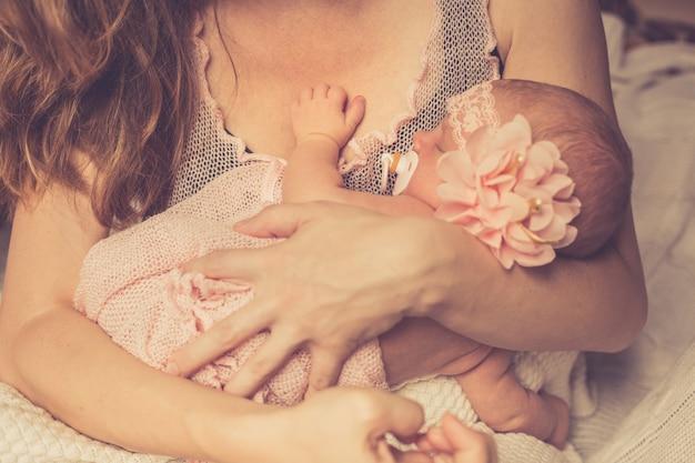 Mãe mantém seu adorável bebê recém-nascido adormecido nos braços e olha para ela.