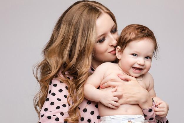 Mãe, mantendo o filho nas mãos e beijar criança