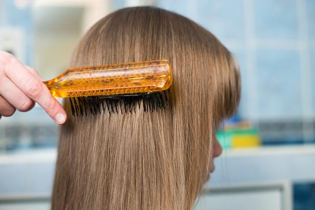 Mãe mão com escova penteando o cabelo longo loiro de menina criança bonito após o banho no fundo desfocado interior.