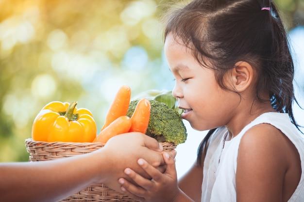 Mãe mão dando cesta de legumes para menina criança e ela cheirando Foto Premium