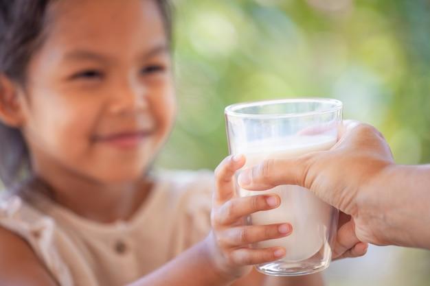 Mãe mão dando copo de leite para seu filho com carinho e amor
