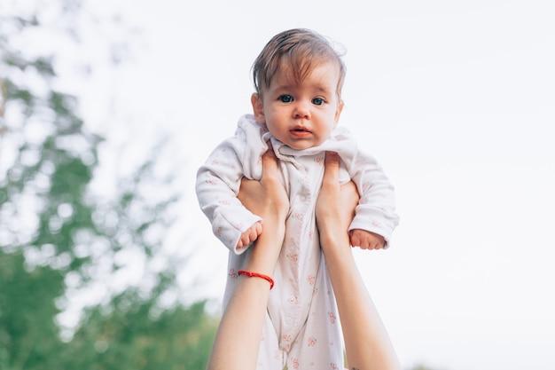 Mãe mãos jogando o ar alto alegre bebê.