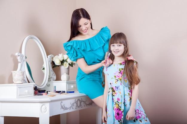 Mãe maquiando sua linda filha pré-adolescente